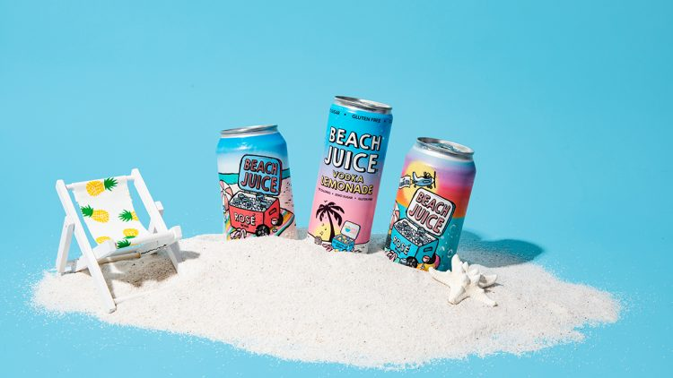 cans of beach juice in sand