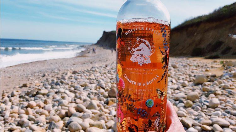 A bottle of Summer In A Bottle on the beach